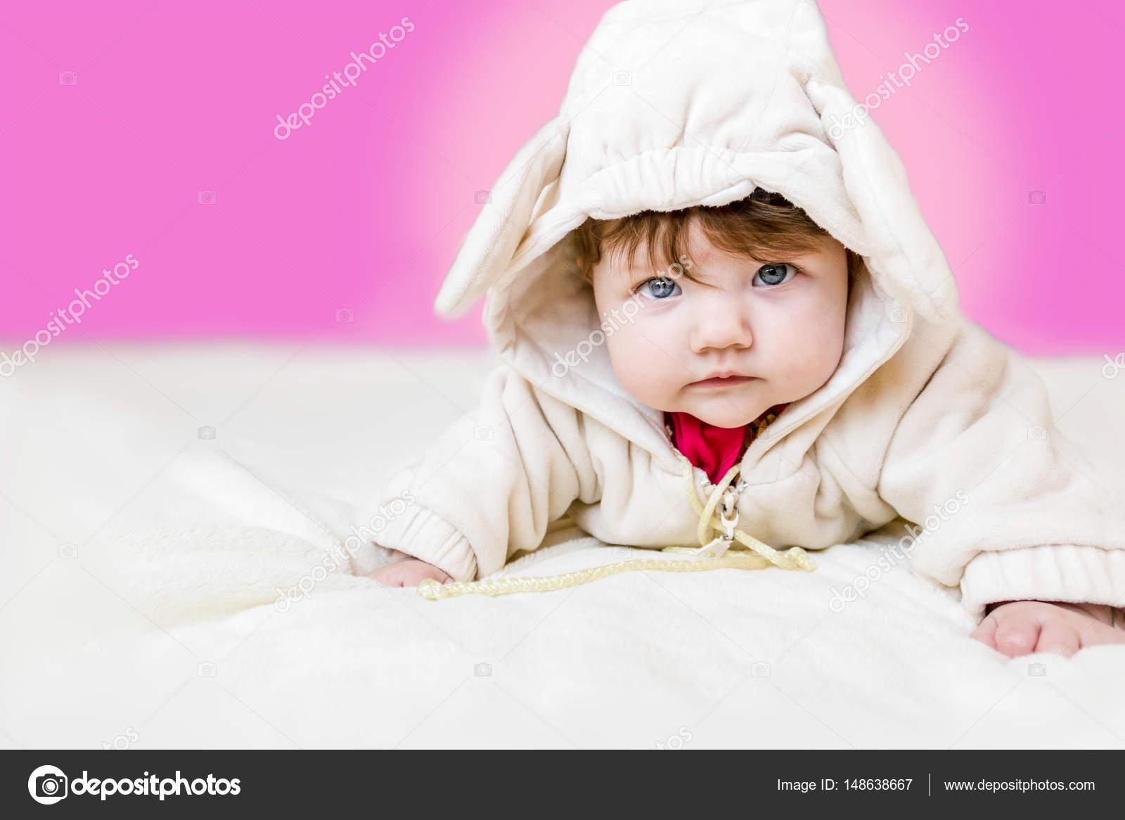 Mooie een baby meisje liggend op haar buik in een pak met oren