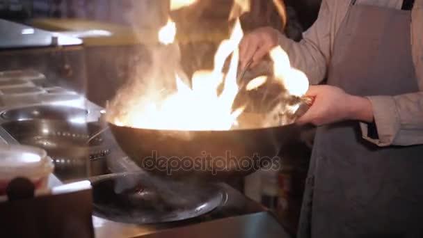 Kuchař, vaření s ohněm při smažení Pan.Professional šéfkuchaře v komerční kuchyni vaření Flambe stylu. Vaření Asijské nudle.