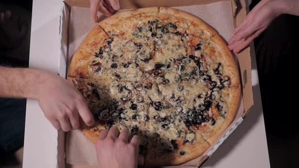 Pohled shora na oh ruce přinést a rozvoz pizzy jedí pozdě. Noční práce a potravin courier