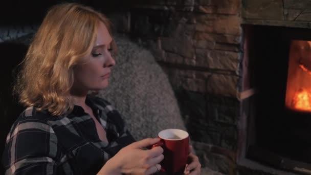 Mladá krásná žena se těší zimní horkým nápojem relaxovat u krbu doma, zblízka střílel