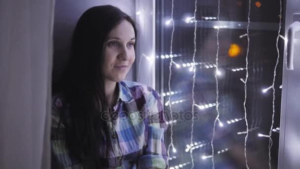 Krásná přitažlivá žena, sedící na okenní parapet zdobí věnce. Nový rok, Vánoce, dovolená Concept