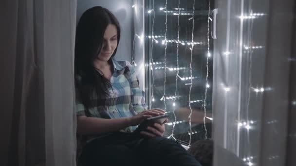 Nádherný atraktivní žena pomocí Tablet Pc a sedí na okenní parapet zdobí věnce