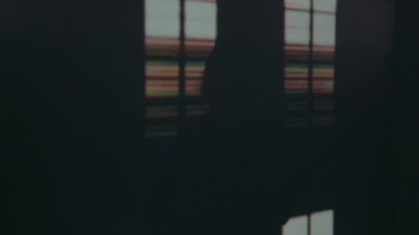 Stín kytarista na scéně. Tmavé pozadí, kouř, reflektory
