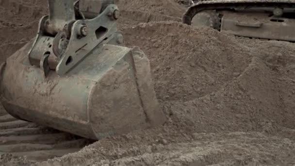 Rypadlo kopání písku a prachu pracovat během práce na silnici, zblízka Shot vědro zemi Mover kopání stroje