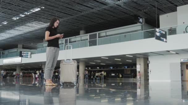 Mladá krásná podnikatelka pomocí Smartphone na letišti při její fronty čekání na registraci, cestování koncepce