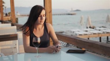 Young Brunette With Glass of Red Wine Using Her Smartphone While Sitting In Cafe By The Sea at Sunset
