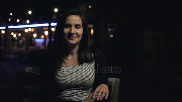 Mladá, krásná krásná bruneta s úsměvem a Pózování na ulici v noci