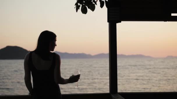 Silueta mladá žena pít červené víno na venkovní terasu dívat na krásný západ slunce u moře