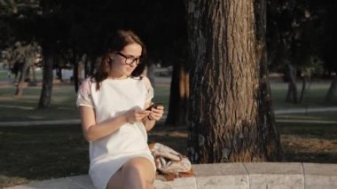 Young Smiling Woman Using Smartphone Sitting on Bench In Park At The Sunset. Beautiful European Girl Texting on Phone