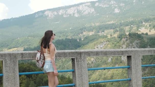 A turista lány állt a híd Djurdjevic, Montenegróban, utazási életmód oldalnézete