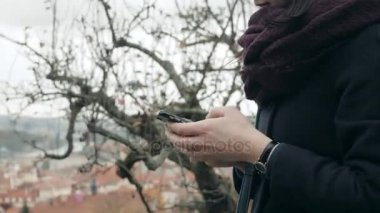 Close Up of Womans Hands Using Smartphone Sitting On Bench In Park. Beautiful European Girl Texting On Phone
