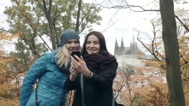 Dvě hezká a šťastná mladá žena dělat Selife s mobilním telefonem v parku na podzim. Nejlepší přátelé uživatele udělat Selfie