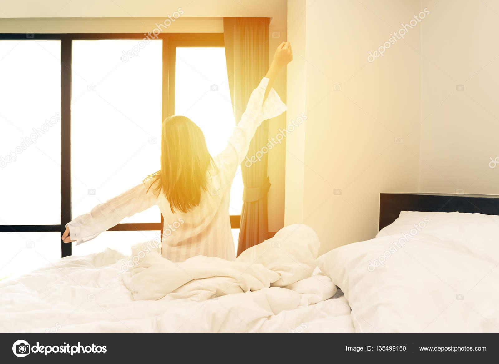 vue arrière de la femme qui s'étend dans son lit après wake up