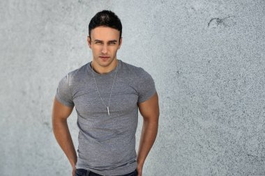 Portrait of young adult handsome man wearing grey casual shirt and posing near grey wall. Handsome man posing and looking at the camera outdoors.
