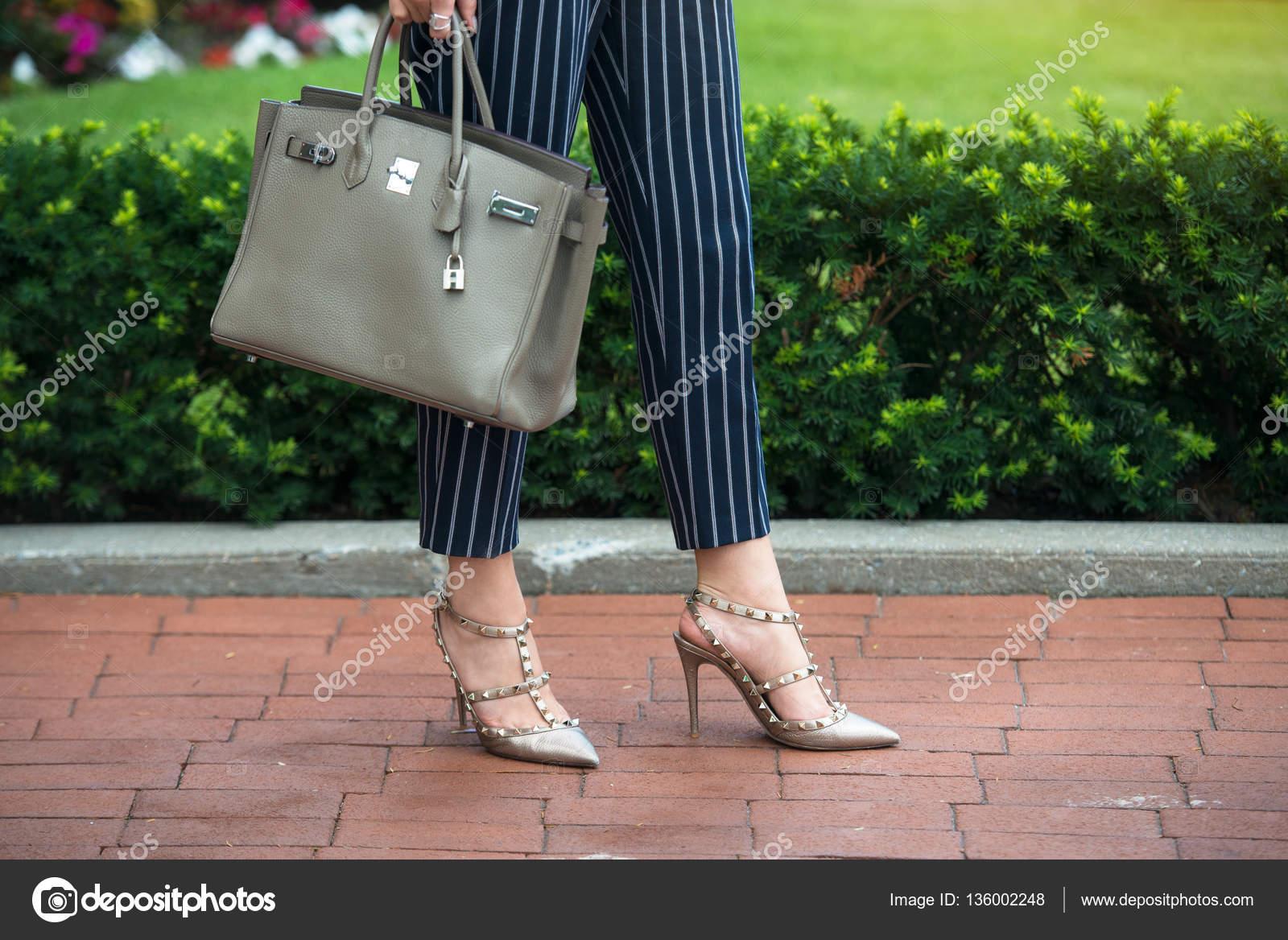 b738cf6a4e Üzletasszony nyári ruhát office. Divatos nő magas hells cipőben, kék-fehér  csíkos pamut nadrág, és tartsa lenyomva a sötétszürke táska szabadban —  Fotó ...