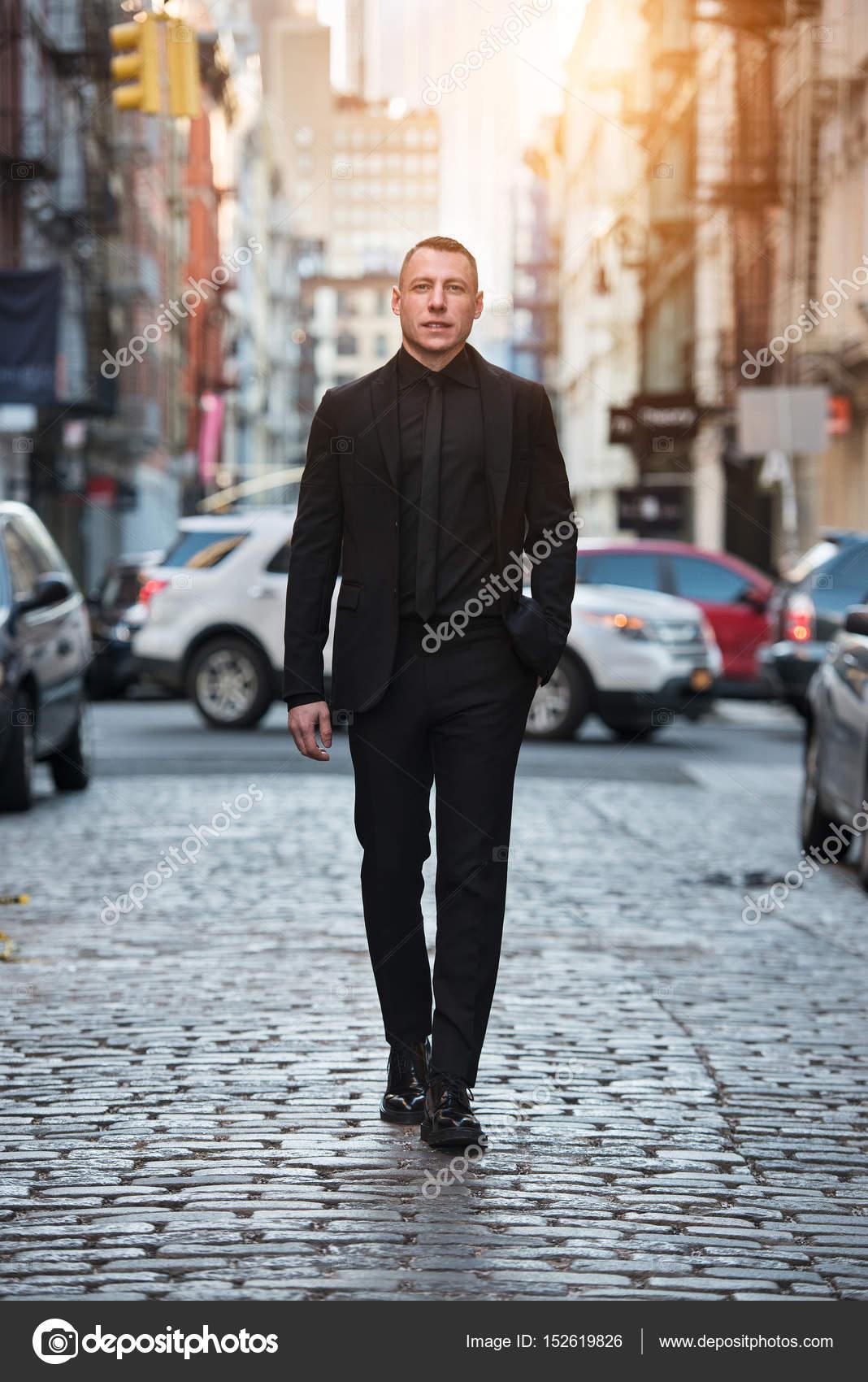 Retrato de cuerpo entero del empresario adulto caminando en traje negro con  calle de la ciudad 83c83bbc2e6