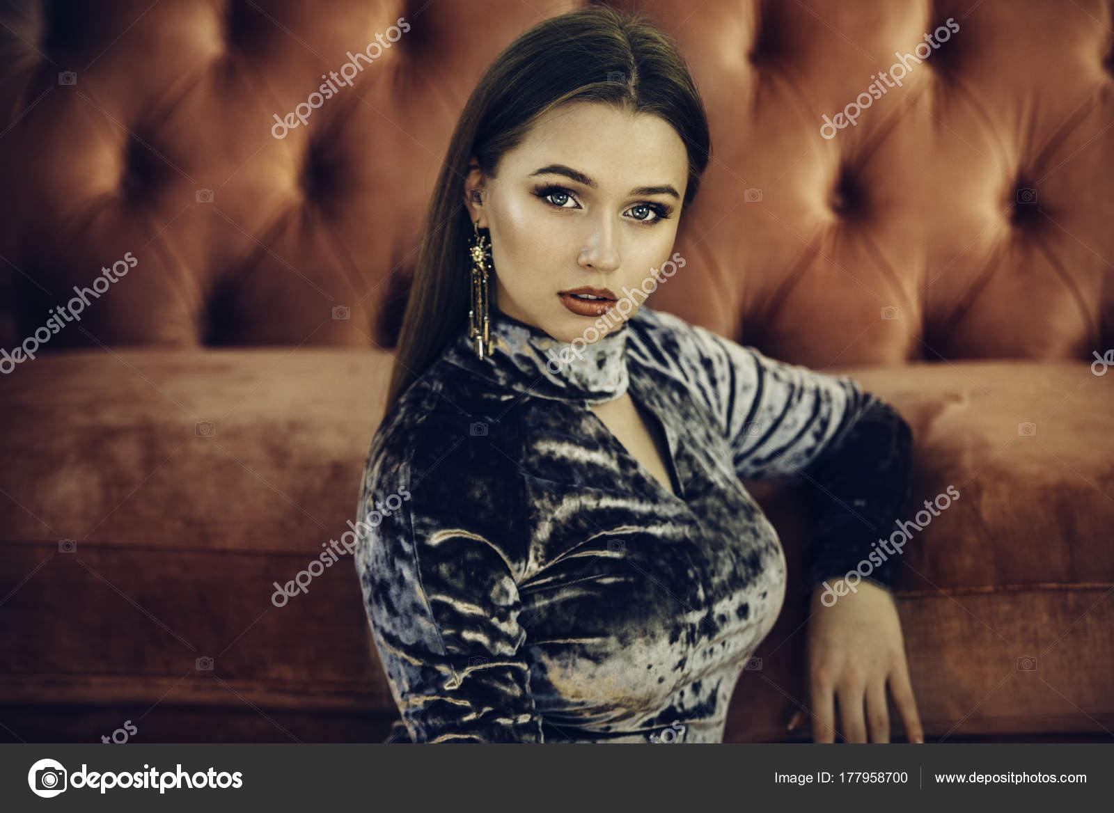 084bcb0803c1 Krásná žena nosí luxusní večer šaty a náušnice s make-upem pózuje na  červené pohovce– stock obrázky