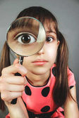 Little girl searching  with magnifying glass