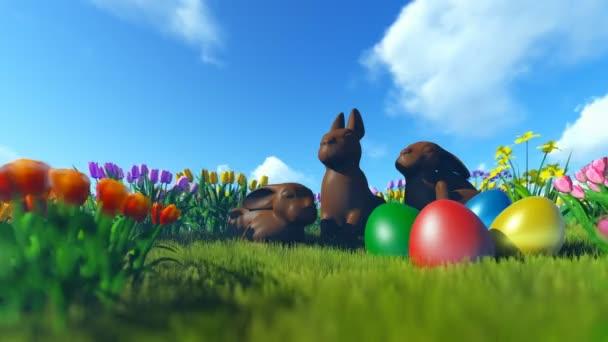 Velikonoční vajíčka a čokoládové zajíčky na zelené louce s barevnými tulipány