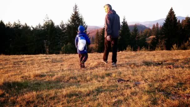 Otec a syn na výlet, západ slunce, pohled zezadu