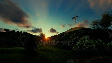 Woman praying over Jesus cross against beautiful timelapse sunrise
