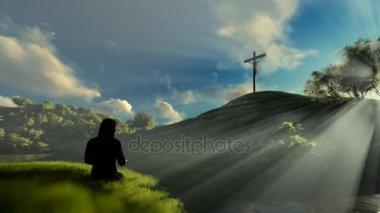 Woman praying at Jesus cross against beautiful sun rays, panning