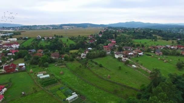 Letecké panorama horské vesnice s holuby před kamerou