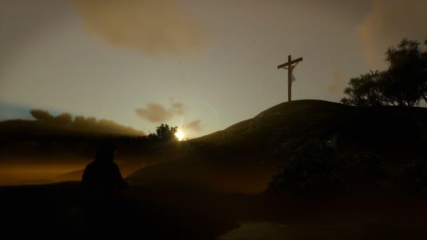 Christian woman praying at Jesus cross at sunset, panning, 4K