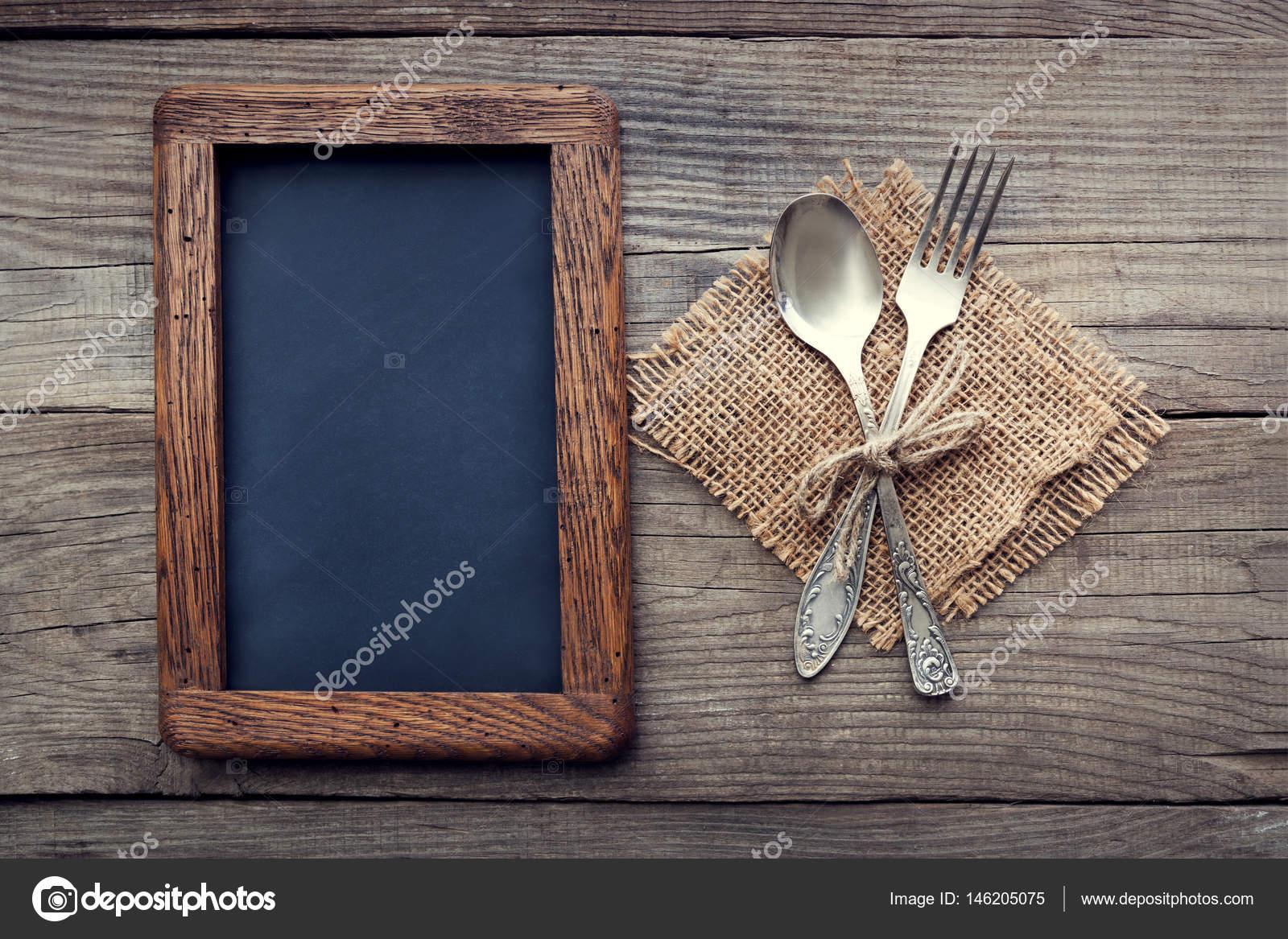 Gabel und Löffel auf einem rustikalen Tisch mit groben Rahmen für ...