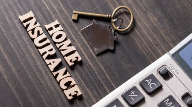 Home Insurance with house key and calculator on wooden table top
