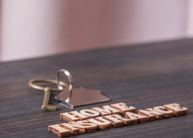 Home Insurance text with house key on wooden table top.