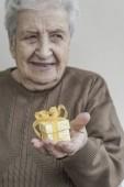 Starší žena držící malý dárek