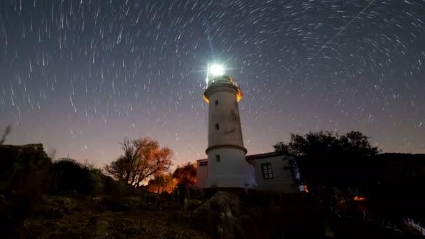4k. Zeitraffer einer wunderschönen nächtlichen Landschaft mit Leuchtturm mit rotierendem Sternenhimmel auf einem Hintergrund