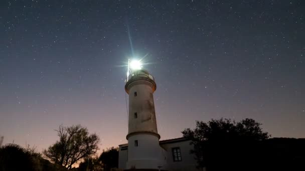 Timelapse z krásné noční krajina s majákem s rotujícím hvězdnou oblohou na pozadí