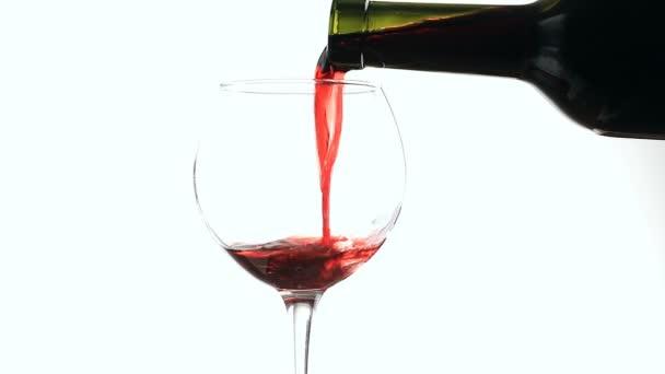 nalévání červeného vína do sklenky na bílém pozadí