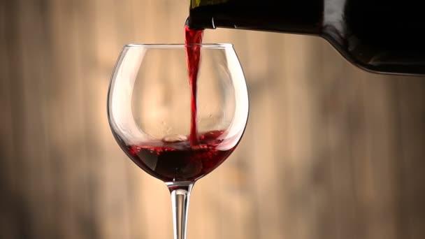 Rotwein in ein Glas gießen.
