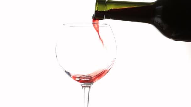 nalévání červeného vína do sklenky na bílém pozadí.
