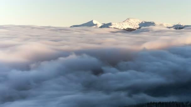 Zimní krajina v Karpatských horách. Krásný západ slunce nad mraky.