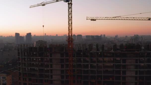 Letecký záběr budovy v procesu výstavby. Práce na velkém staveništi. V pozadí Pracovní jeřáb a město.