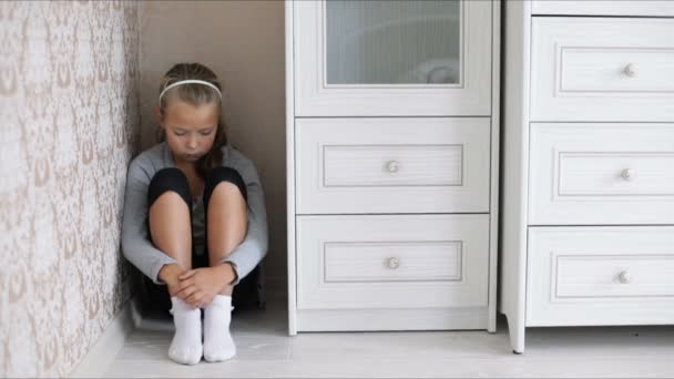Little sad girl sitting on the floor