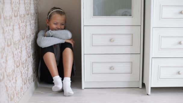Little girl sitting in the corner of a room