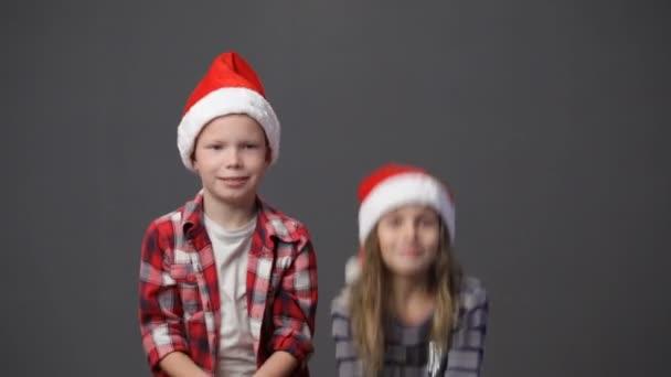 Roztomilý chlapec a dívka v vánoční čepice vyhazoval konfety