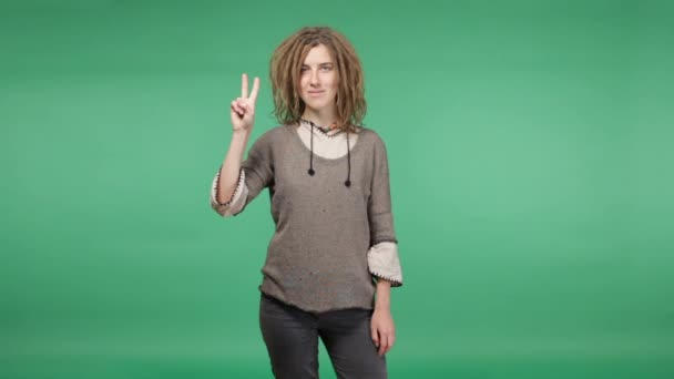 Beautiful hipster woman with dreadlocks showing peace