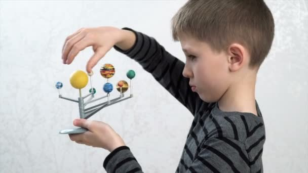 boy turning the models of planets