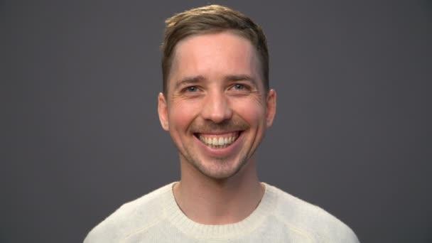 muž v bílém svetru široce usmívat