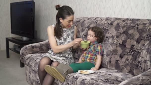 Mladá matka krmí svou malou dcerou z mísy
