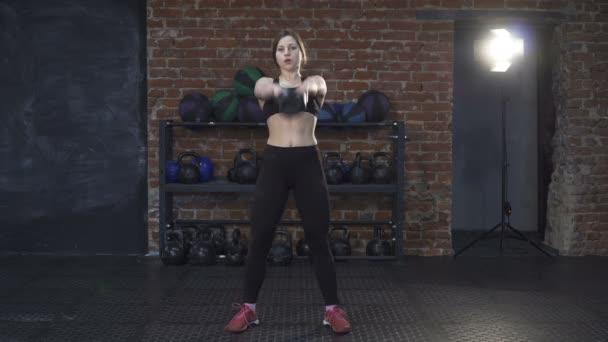 Fitness žena dělá kettlebell houpačky
