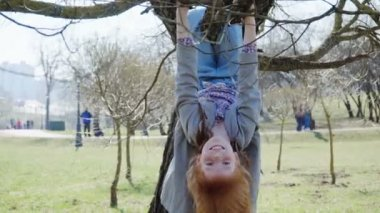 Red-haired girl is playing in a sunny park