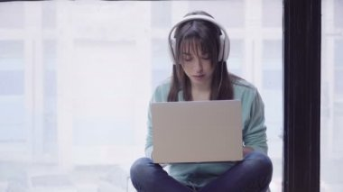 woman in headphones working on a laptop