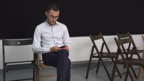 business man in empty conference room touching smartphone